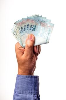 100 reais banknotów brazylii trzymanych przez męską rękę na na białym tle.