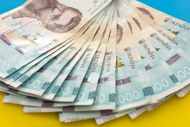 1000 nowych banknotów ukrainy na żółtym niebieskim tle. koncepcja oszczędzania i pieniędzy. ukraińskie pieniądze.