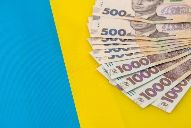 1000 nowych banknotów ukrainy na żółtym niebieskim tle. oszczędź i pieniądze cocncept. ukraińskie pieniądze.