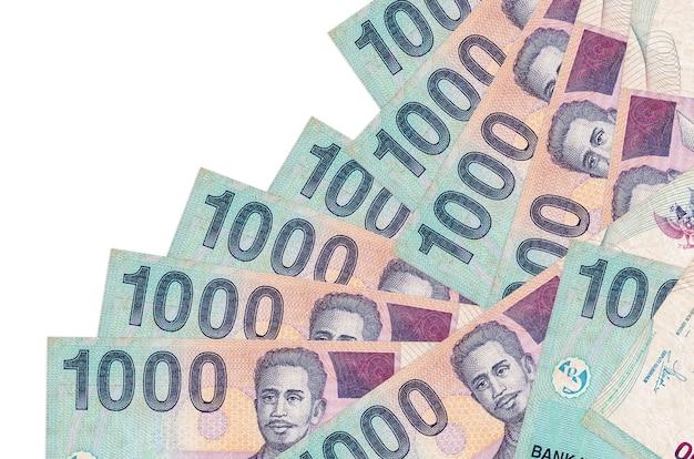 1000 rachunków rupii indonezyjskiej leży w innej kolejności na białym tle. lokalna bankowość lub koncepcja zarabiania pieniędzy.