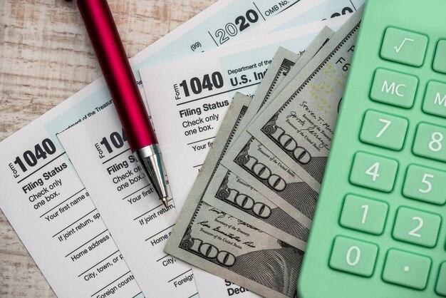 1040 formularz podatkowy, kalkulator i długopis w dolarach amerykańskich