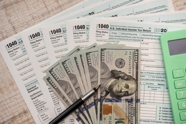 1040 formularz podatkowy w usa z długopisem i dolarami na biurku. obliczanie zwrotu podatku