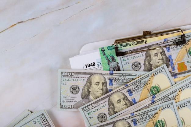 1040 formularz podatkowy z czekiem refundacyjnym i gotówką czek na zwrot bodźca w postaci stu rachunków w dolarach amerykańskich