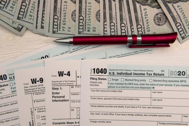 1040 formularz podatkowy z długopisem i rachunkami w dolarach amerykańskich, koncepcja finansowa