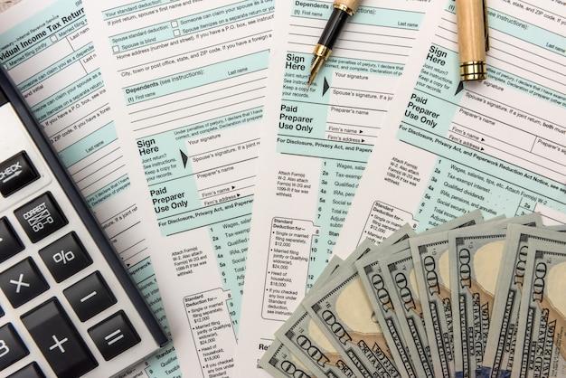 1040 formularz podatkowy z pieniędzmi i kalkulatorem. pojęcie podatku.