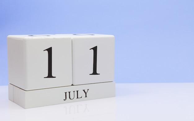 11 lipca. dzień 11 miesiąca, dzienny kalendarz na białym stole z odbiciem, z jasnoniebieskim tłem.