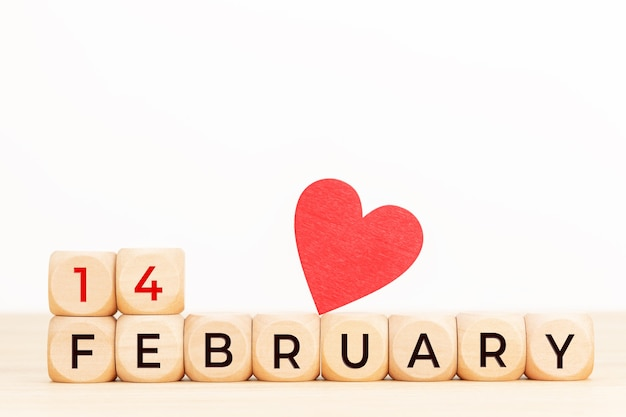 14 lutego tekst na drewnianych klockach i serce na stole. koncepcja walentynki.