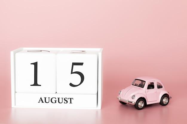 15 sierpnia, dzień 15 miesiąca, kostka kalendarza na nowoczesnym różowym tle z samochodem