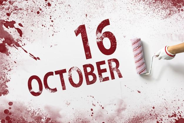 16 października. 16 dzień miesiąca, data kalendarzowa. ręka trzyma wałek z czerwoną farbą i pisze datę w kalendarzu na białym tle. jesienny miesiąc, koncepcja dnia roku.