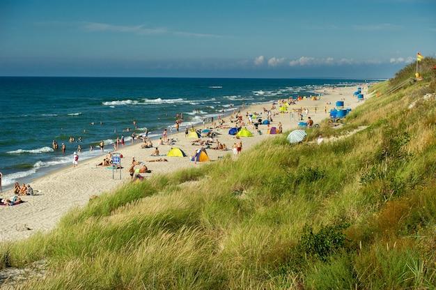 17 sierpnia 2017 r., nida, litwa. zatłoczona plaża w upalny, jasny letni dzień na mierzei kurońskiej morza bałtyckiego