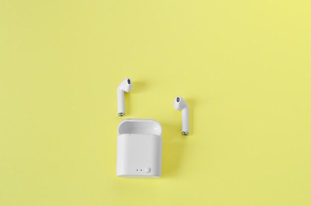 2 białe bezprzewodowe słuchawki douszne z bluetooth na żółtej ścianie. miejsce na kopię. leżał płasko.