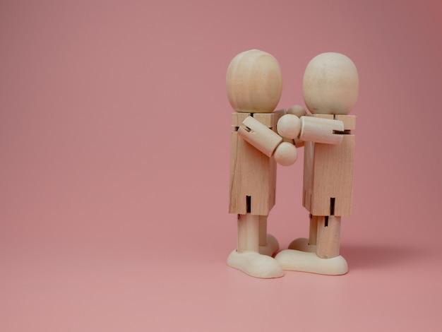 2 drewniane lalki przytulające się na różowym tle. koncepcja kontaktu społecznego od drewnianych lalek.