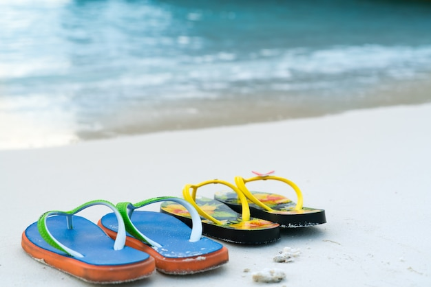 2 kapcie na białej, piaszczystej plaży, czas podróży i wakacji