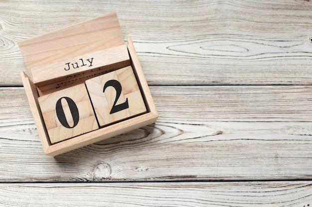 2 lipca drewniany, kwadratowy kalendarz. podróż służbowa lub planowanie wakacji