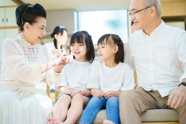 2 małe wnuczki rozmawiające z dziadkami w pokoju