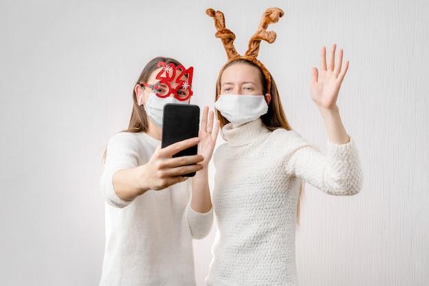 2 młode dziewczyny lub młoda kobieta w czapce mikołaja i masce na twarz robią rozmowę wideo online. kwarantanna