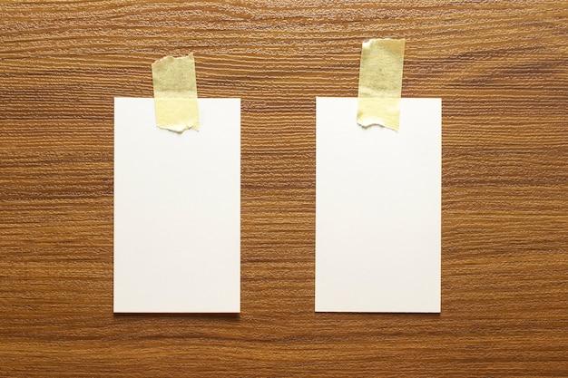 2 puste wizytówki przyklejone żółtą taśmą do drewnianej powierzchni o wymiarach 3,5 x 2 cale