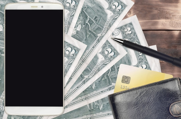 2 rachunki w dolarach amerykańskich oraz smartfon z torebką i kartą kredytową. e-płatności lub koncepcja e-commerce.