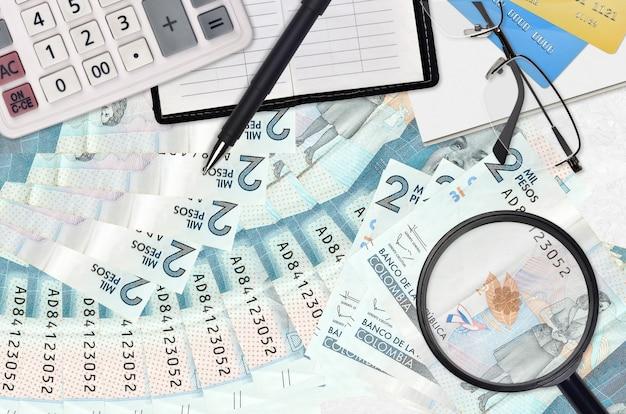 2 rachunki w peso kolumbijskich i kalkulator z okularami i długopisem. koncepcja sezonu płatności podatku lub rozwiązania inwestycyjne. poszukiwanie pracy z wysokimi zarobkami