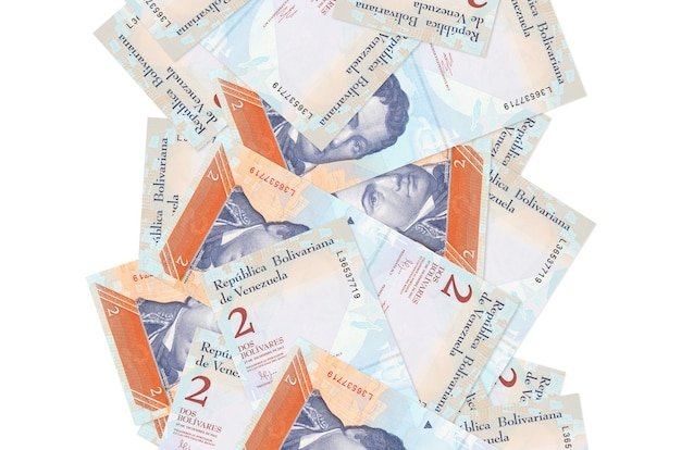 2 wenezuelskie boliwary lecące w dół na białym tle. wiele banknotów spada z białą przestrzenią na kopię po lewej i prawej stronie
