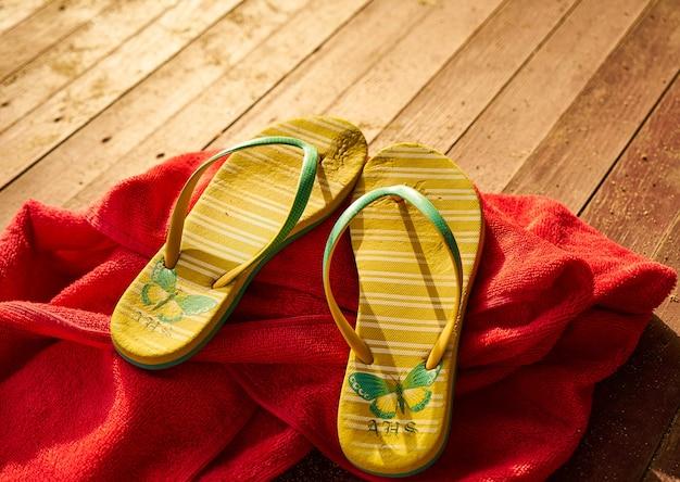 2 żółte sandały i czerwony ręcznik