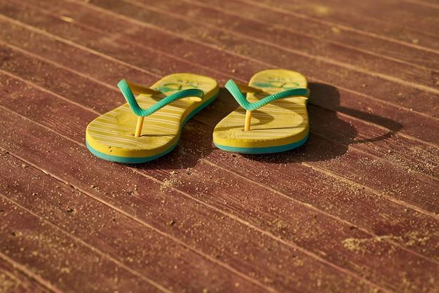 2 żółte sandały na drewnie