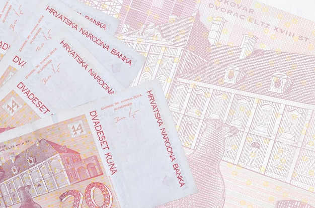 20 banknotów kuny chorwackiej leży w stosie na ścianie dużego półprzezroczystego banknotu. streszczenie ściany biznesu z miejsca na kopię