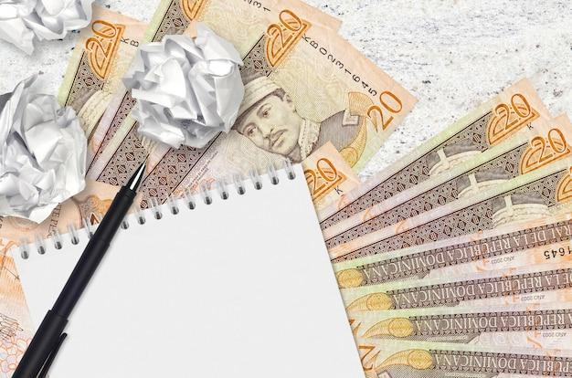 20 banknotów peso dominikańskich i kulki zmiętego papieru z pustym notatnikiem. złe pomysły lub mniej pomysłów na inspirację. poszukiwanie pomysłów na inwestycje