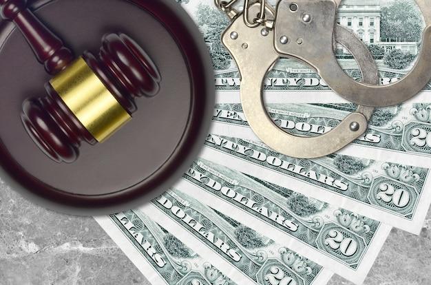 20 dolarów amerykańskich i młotek sędziowski z policyjnymi kajdankami na ławce sądu. pojęcie procesu sądowego lub przekupstwa. unikanie opodatkowania lub uchylanie się od opodatkowania
