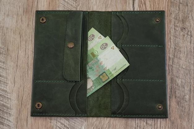 20 hrywien w portfelu kobiety na drewnianej powierzchni
