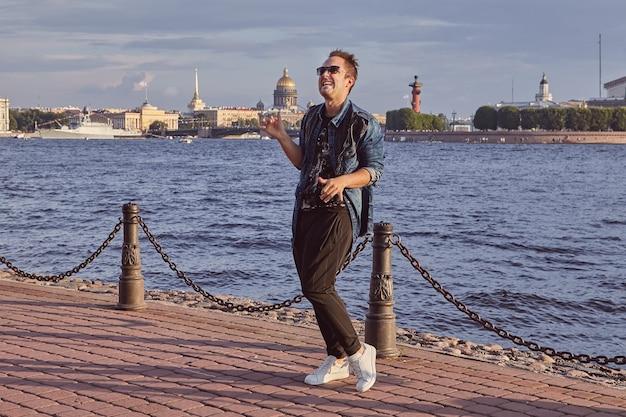 20-letni mężczyzna tańczy na nabrzeżu newy podczas wycieczki do sankt petersburga.