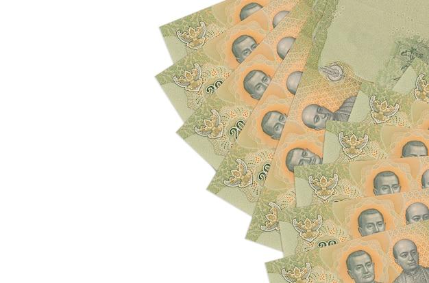 20 rachunków bahtów tajskich leży na białym tle