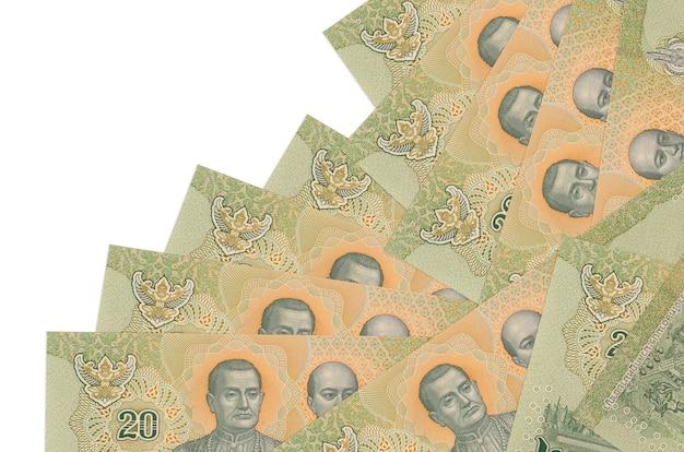 20 rachunków bahtów tajskich leży w innej kolejności na białym tle