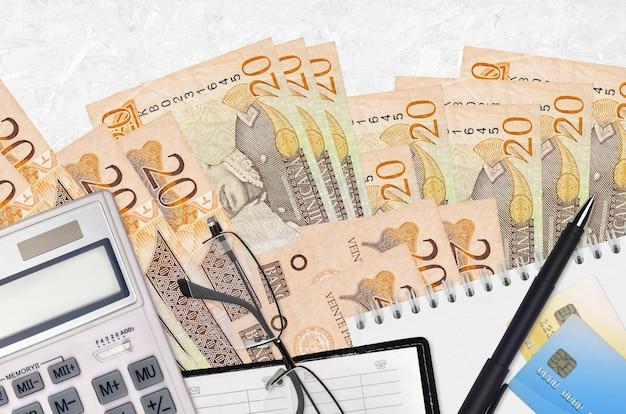 20 rachunków peso dominikańskich i kalkulator z okularami i długopisem