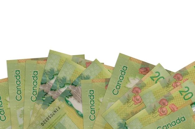 20 rachunków w dolarach kanadyjskich leży w dolnej części ekranu na białym tle