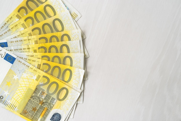 200 banknotów euro w wachlarz na drewnianym stole