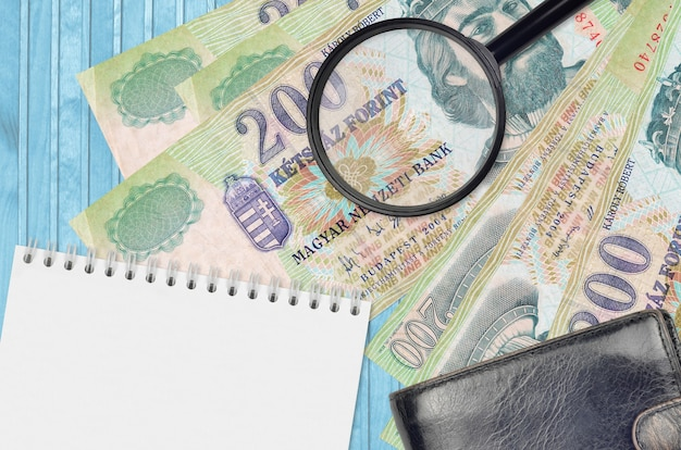 200 banknotów forintów węgierskich i szkło powiększające, czarna torebka i notatnik.