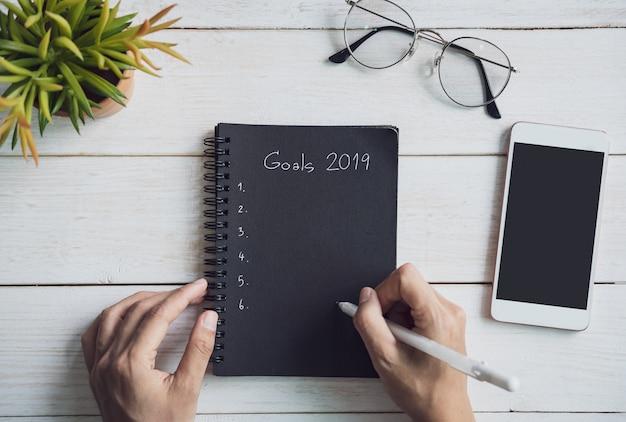2019 celów tekst na notatniku z smartphone na białym drewnianym biurku, odgórny widok