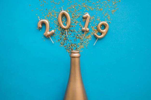 2019 napis z świece z butelki na stole