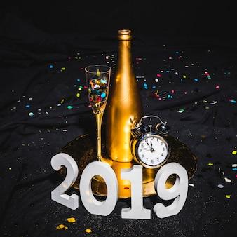 2019 postaci stoi blisko tacy z butelką
