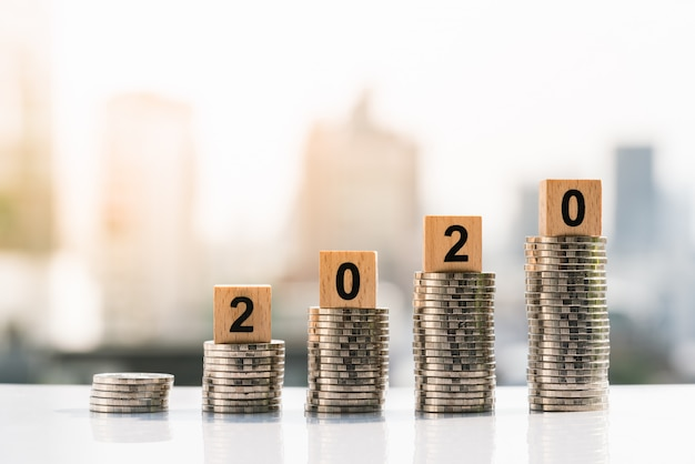 2020 drewniane klocki na szczycie stosu monet na tle miasta.