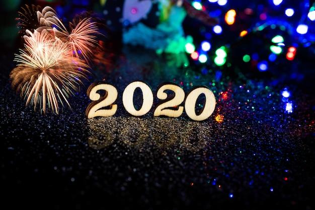 2020 ozdób choinkowych, świerkowe gałęzie na ciemnym tle drewnianych