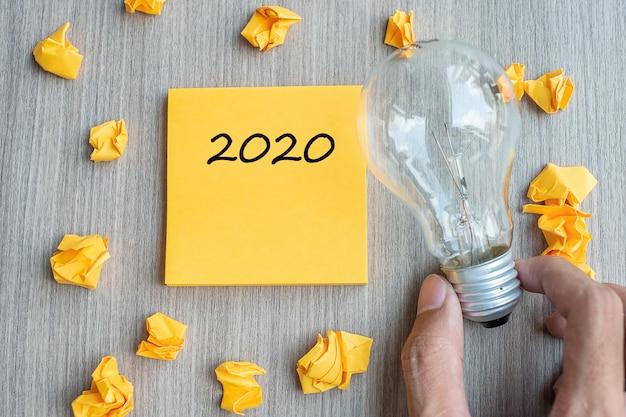 2020 słów na żółtej notatce i pokruszonym papierze z żarówką