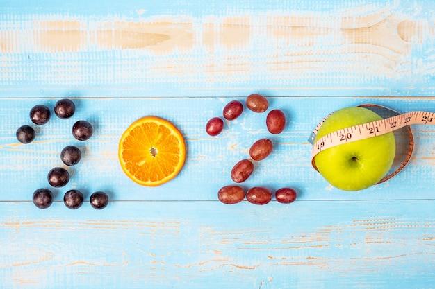 2020 szczęśliwego nowego roku i nowego z owocami czerwone tła