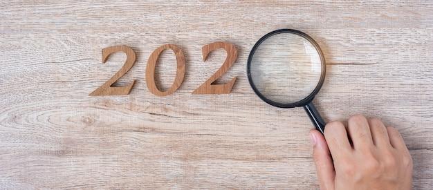 2020 szczęśliwego nowego roku z biznesmenem trzyma szkło powiększające
