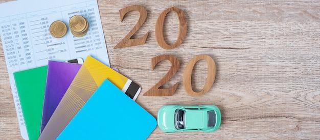 2020 szczęśliwego nowego roku z książką banku i samochodem na stół z drewna