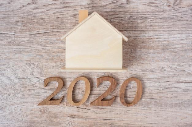 2020 szczęśliwego nowego roku z modelu domu na stole z drewna