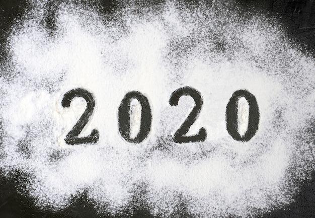 2020 tekst wykonany z mąki z dekoracjami na czarnym tle.