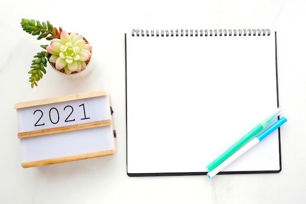 2021 na drewnianym pudełku, czysty notatnik na białym marmurowym blacie