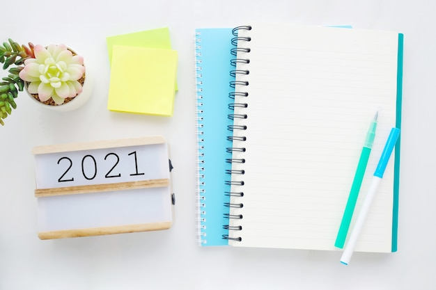 2021 na drewnianym pudełku, czysty notatnik na tle białego marmuru stołu